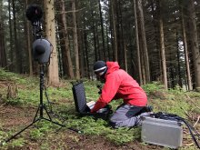 The artist is knelt by an equipment case in a forest, wearing outdoors clothing and setting up a microphone rig. Next to him is a binaural microphone and other equipment cases.